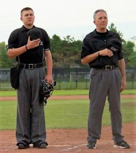 Two-umpire system national anthem with no catcher at Bernie Arbour Stadium (flag behind home plate)